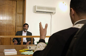 Saddam Hussein sits before an Iraqi judge at a courthouse in Baghdad, 1 July 2004.